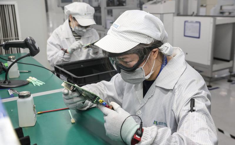 中国江苏省南通市一家电子厂的工人戴着口罩复工。