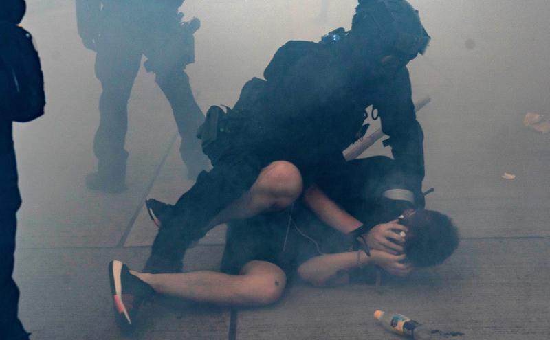 2019年10月香港示威者在催泪弹散发的烟雾中被港警逮捕。
