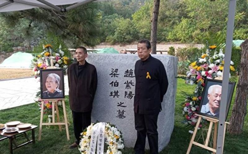 2019年10月18日,赵紫阳夫妇墓碑前摆放着出席骨灰安葬仪式的亲友们献的鲜花。赵紫阳之子赵二军(右)立于碑前。(美国之音)