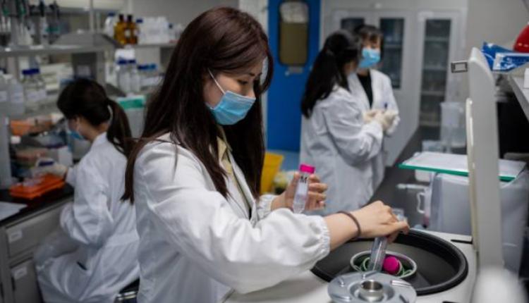 图为北京一家科技公司人员在测试疫苗