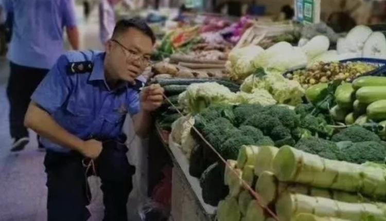 执法人员在菜市场丈量菜摊面积