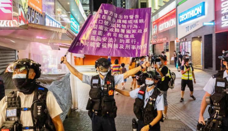 8月11日,防暴警察在争取新闻自由的活动中升起港区国安法的警告旗