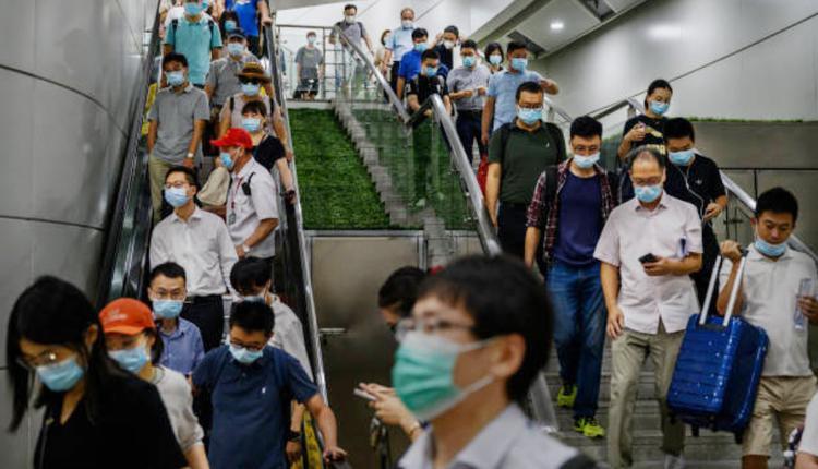 疫情升温期间民众配戴口罩在北京南站。