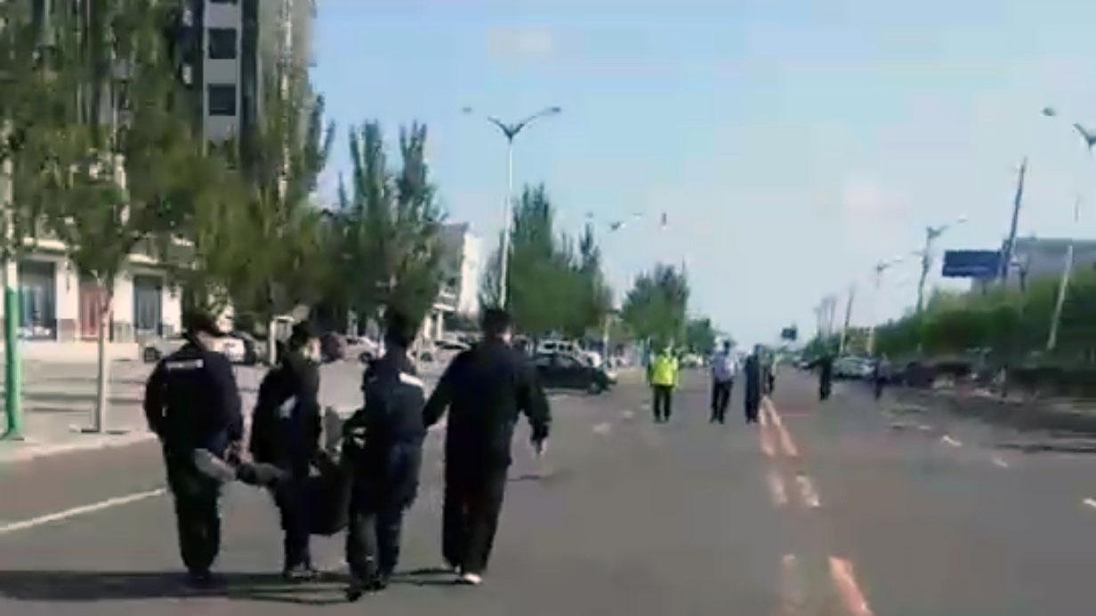 科尔沁左翼后旗一学生家长被4名公安抬向警车。(志愿者提供/记者乔龙)