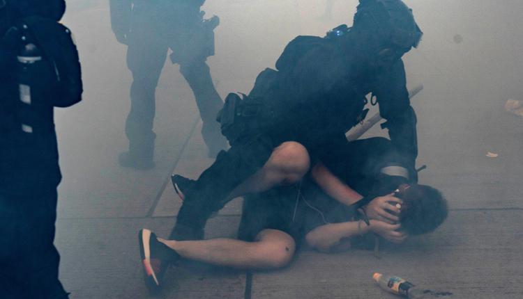 图为2019年10月香港示威者在催泪弹散发的烟雾中被港警逮捕