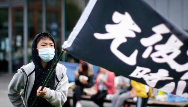 """港人挥舞著""""光复香港,时代革命""""的旗帜"""