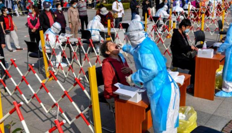 10月12日山东青岛一名工作人员正在为市民做核酸检测