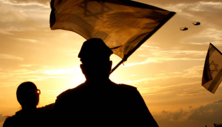 图为以色列民众在夕阳下挥舞国旗