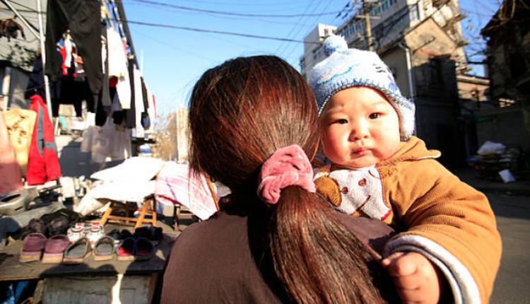 图为一位妈妈带着孩子走在上海街头