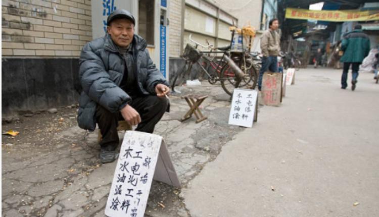 中国江苏的一位民工正在街边招揽零活