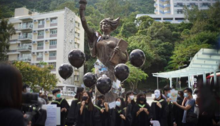 香港中文大學畢業生手持黑色氣球在民主女神像前合影