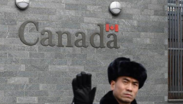 图为位于北京的加拿大大使馆外保安在阻止拍照