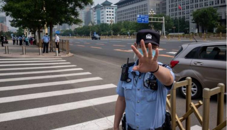 图为北京警察阻止记者拍照