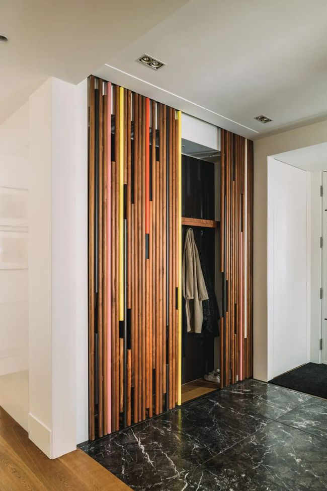 在彩色木条门后有一个隐藏式的衣帽柜,不拉开还以为只是一个装饰,非常有新意。