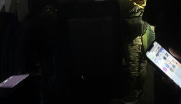 列车内几乎没有灯光,有乘客利用手机来照明。