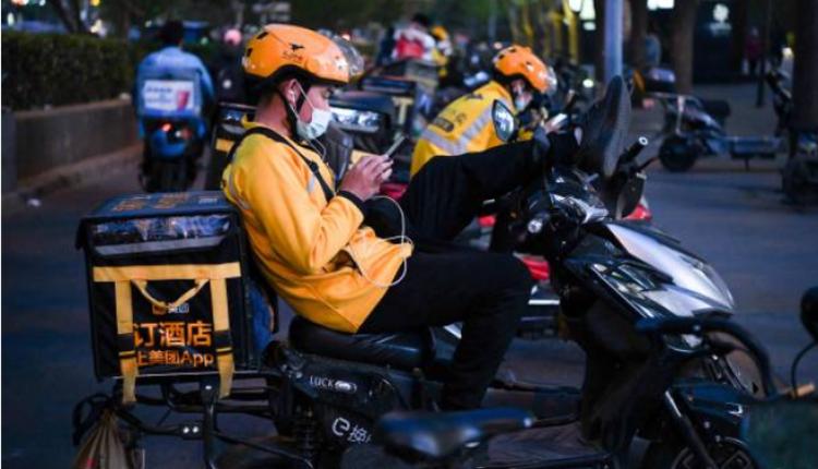美团外卖小哥在北京的街头休息
