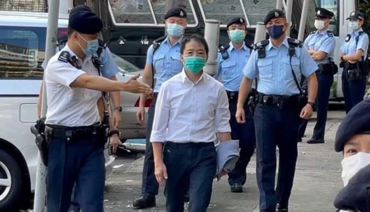 获准短暂保释的胡志伟在警方陪同下,由荔枝角收押所前往殡仪馆送别亡父。