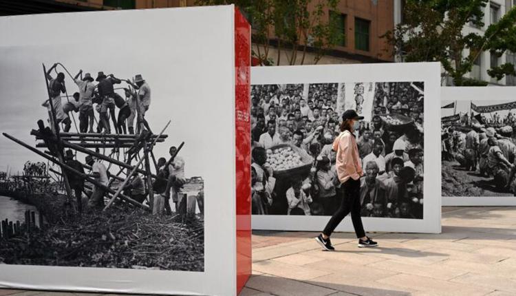 6月12日,北京一名女子走到中共百年图片展。