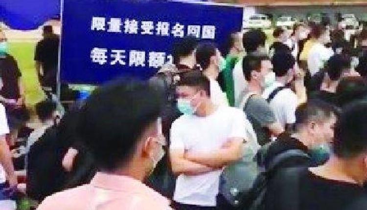 """云南某边境口岸被迫立起""""限量接受报名回国,每天限额150人""""的公告牌。"""