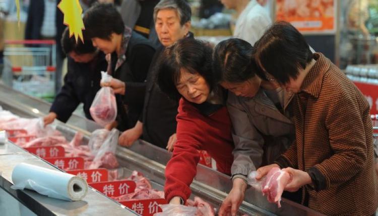 图为中国民众在挑选猪肉