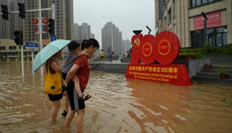 郑州市民淌水路过中共建党百年的宣传牌