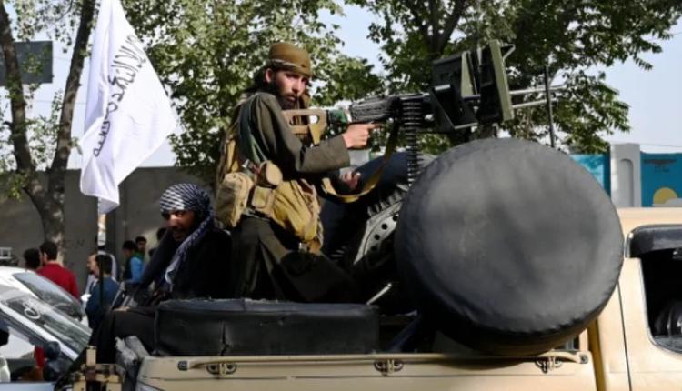 在军事接管阿富汗喀布尔后,手持枪枝的塔利班成员站在一辆车上