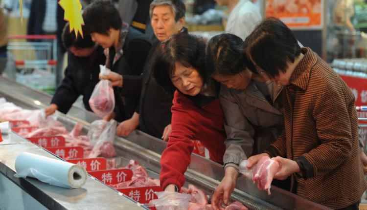 图为中国市民在市场挑选猪肉