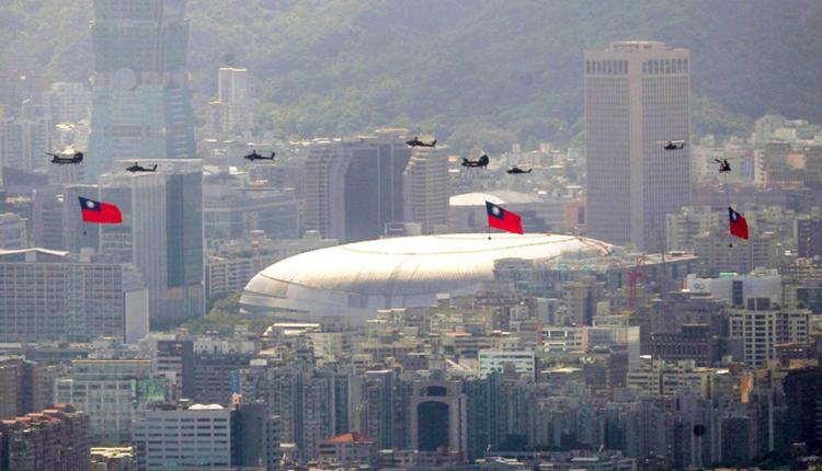 国军直升机吊挂3面国旗通过台北小巨蛋上空。